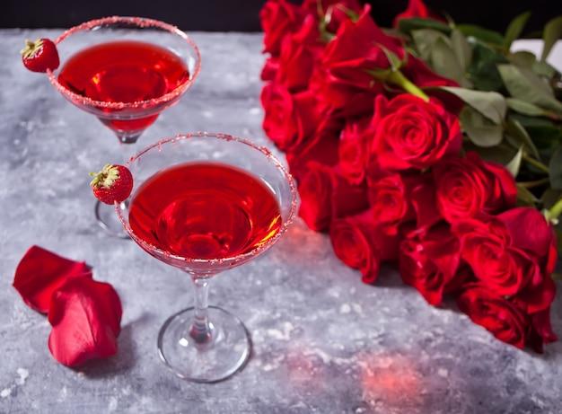 Cocktail alcoólico exótico vermelho em vidro transparente e rosas vermelhas para jantar romântico.