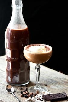 Cocktail alcoólico ice scream russian é servido em uma garrafa de vidro e um cálice na mesa de madeira em fundo preto