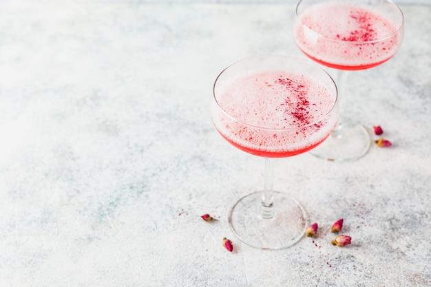 Cocktail alcoólico rosa com limonada, champanhe ou martini numa taça de champanhe, com espuma e decorado com botões de rosa secos, cocktail tipo daiquiri, cosmopolitan, pink mimosa ou margarita