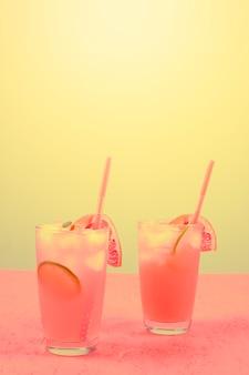 Cocktail alcoólico rosa fresco com toranja; fatia de limão e cubos de gelo contra um fundo amarelo