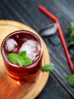 Cocktail alcoólico vermelho com gelo e hortelã em um copo