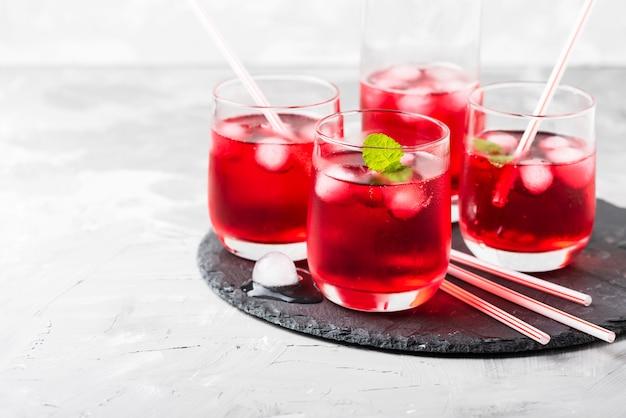 Cocktail alcoólico vermelho com gelo e hortelã