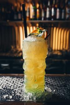 Cocktail amarelo decorado com folha de hortelã