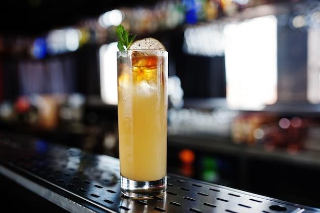 Cocktail amarelo longo alcoólico em vidro na mesa de bar