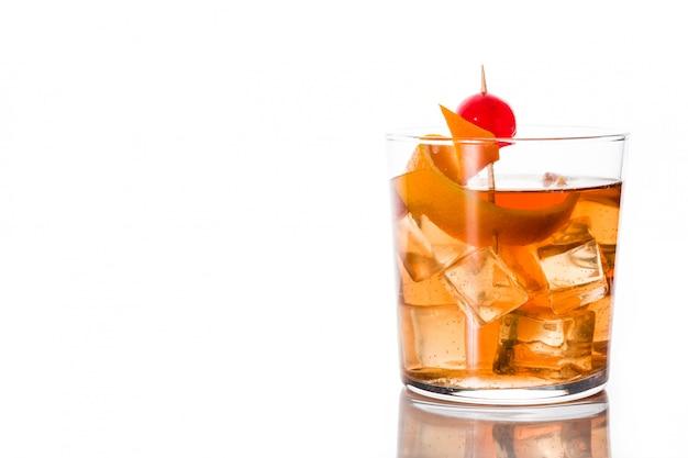 Cocktail antiquado com a laranja e a cereja isoladas no espaço branco da cópia