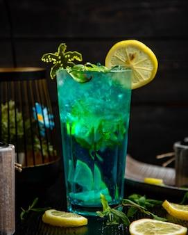 Cocktail azul com hortelã e limão em um copo.