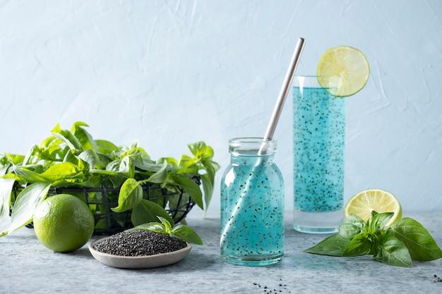 Cocktail azul com sementes de manjericão e suco tropical em vidro na luz. fechar-se.