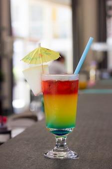 Cocktail brilhante com guarda-chuva e no bar rack