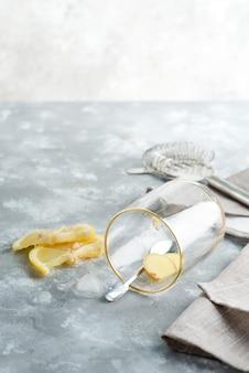 Cocktail caseiro refrescante frio ou limonada de limão em um copo com cubos de gelo em uma mesa de mármore cinza.