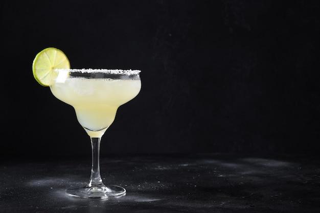 Cocktail clássico de margarita com suco de limão e cubo de gelo em fundo preto