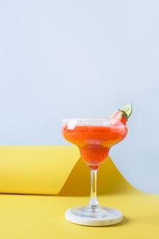 Cocktail clássico de margarita com suco de limão e cubo de gelo na orientação vertical do fundo preto