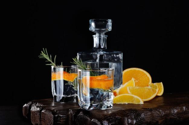 Cocktail clássico dry gin com tônica e raspas de laranja com um raminho de alecrim em uma tábua de madeira com fatias suculentas de laranja