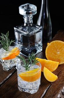Cocktail clássico dry gin com tônica e raspas de laranja com um raminho de alecrim em uma tábua de madeira com fatias suculentas de laranja Foto Premium