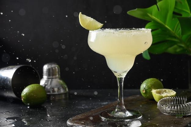 Cocktail clássico margarita com suco de limão e cubo de gelo em fundo preto com respingo