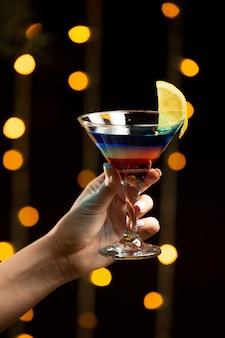 Cocktail colorido com limão na mão.