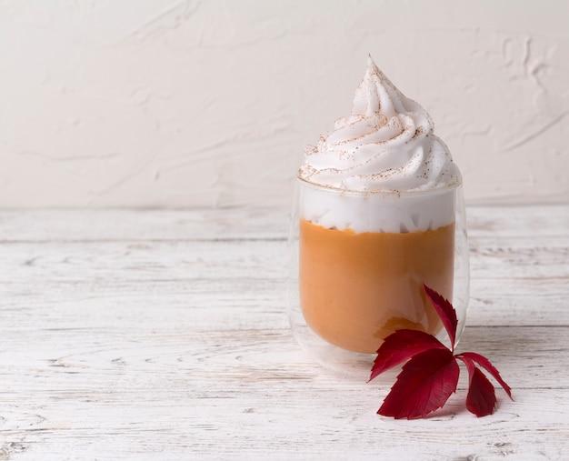 Cocktail com chantilly em cima no fundo branco de madeira