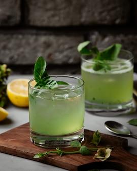 Cocktail com cubos de gelo e folhas