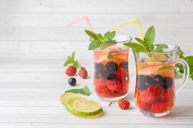 Cocktail com groselha preta, morango, hortelã e limão. bebida refrescante de verão.