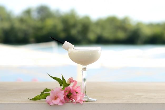 Cocktail com hortelã e gelo em um copo de vidro. com decoração de flores e frutas