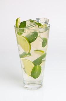 Cocktail com hortelã, limão e gelo picado em um fundo branco