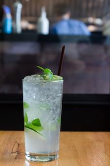 Cocktail com limão e gelo em um fundo claro.