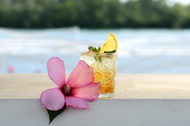 Cocktail com limão e hortelã em um copo. com decoração de flores