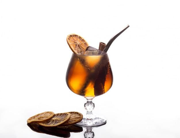 Cocktail com refrigerante de cola, gelo, canela e limão