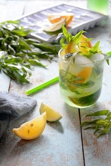 Cocktail com rum, limão, limão e estragão fresco