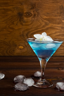 Cocktail cosmopolita azul no fundo de madeira