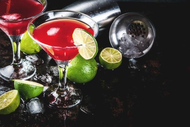 Cocktail cosmopolita vermelho com limão no copo de martini, na cena enferrujada escura