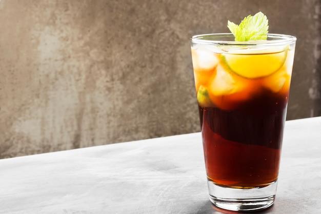 Cocktail cuba libre em um vidro em um fundo escuro. copie o espaço. fundo de alimentos