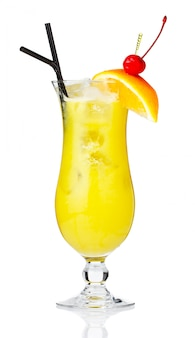 Cocktail de álcool amarelo com bagas e fatia de laranja isolado