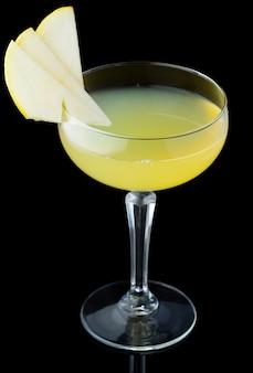 Cocktail de álcool amarelo com fatias de maçã isoladas no fundo preto