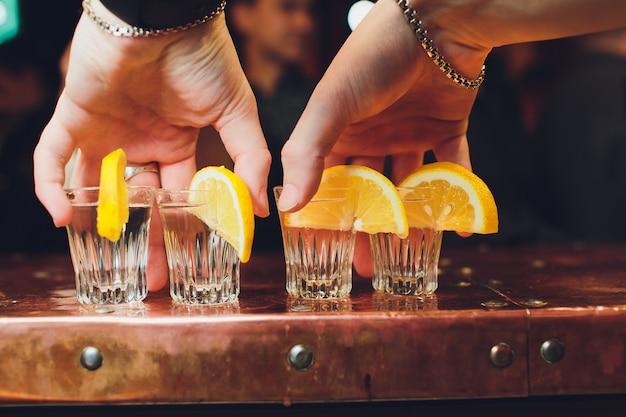 Cocktail de álcool com conhaque, uísque, limão e gelo em copos pequenos, foco seletivo.