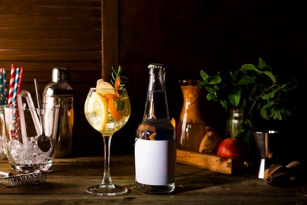 Cocktail de álcool com frutas frescas e com uma garrafa de tônico em fundo de madeira