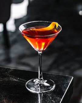 Cocktail de álcool com vista lateral para casca de laranja