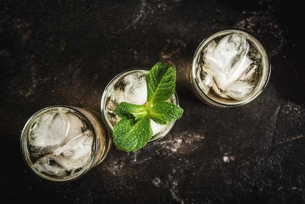 Cocktail de álcool feito de tequila dourada com cubos de gelo e hortelã em uma mesa de concreto preto