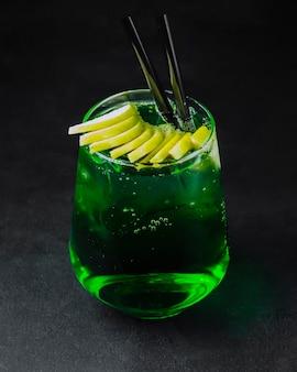 Cocktail de álcool verde com limão fatiado na vista lateral superior