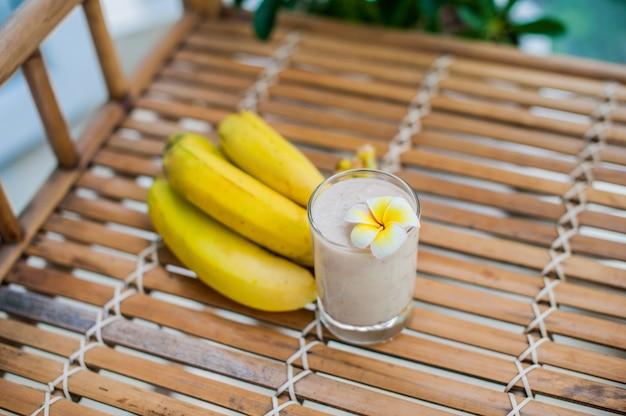 Cocktail de banana e bananas frescas em uma mesa de bambu