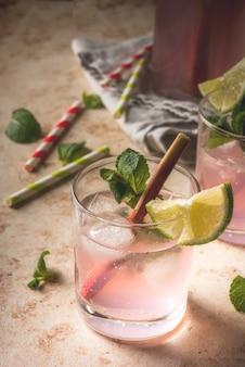 Cocktail de bebida refrescante de verão mojito orgânico caseiro ou limonada com ruibarbo e hortelã em uma mesa de pedra clara em copos e uma garrafa