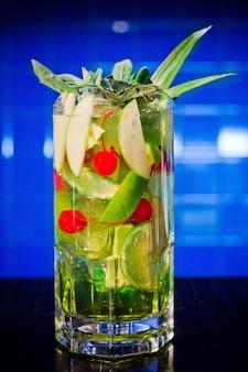 Cocktail de bebida verde com maçã, limão e cereja em frasco grande para grande empresa em azul.