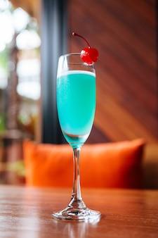 Cocktail de cor turquesa servido com cereja fresca.