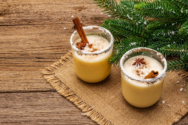 Cocktail de gemada em dois copos dispostos com decoração de natal na mesa de madeira velha. evergreen fer galho de árvore, neve artificial, guardanapo de pano de saco