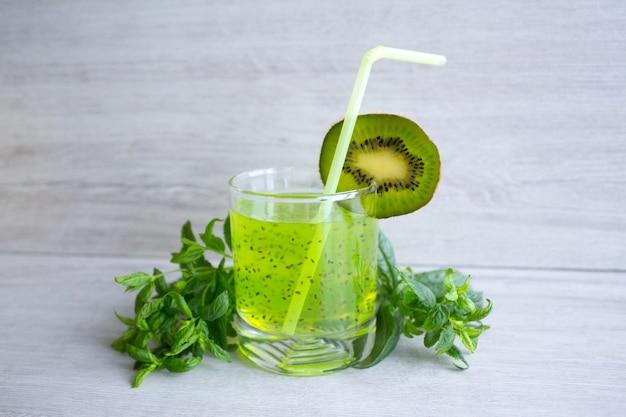 Cocktail de kiwi com sementes e hortelã perfumada verde sobre um fundo claro
