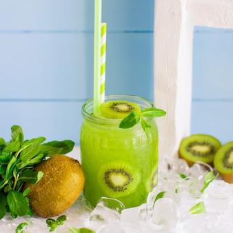 Cocktail de kiwi servido com pedaços de kiwi e gelo em frasco de vidro