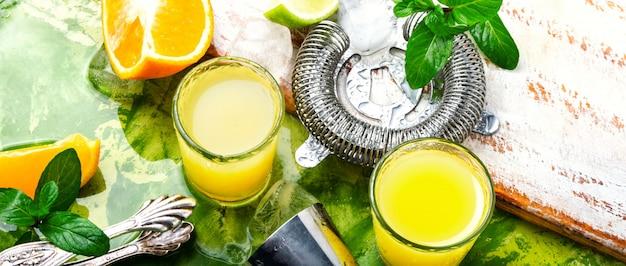 Cocktail de laranja com fatia de limão e gelo. copo de bebida de laranja