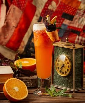Cocktail de laranja fresco servido em um copo com cachimbo e pele laranja descascada e folhas de hortelã fresca.