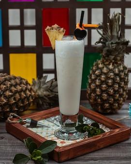 Cocktail de leite de coco com fatia de abacaxi na parte superior