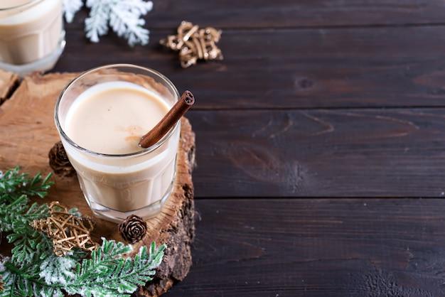 Cocktail de leite de gemada natal, servido em dois copos em uma tábua de madeira com ramo de abeto e pinha em madeira escura. copyspace