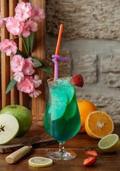 Cocktail de maçã com fatias de maçã e gelo, guarnecido com morango
